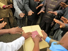 Many hands prayed over the Yemba New Testament, that it would go forth and bear much fruit